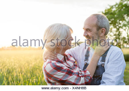 Affectionate senior couple hugging in sunny rural wheat field - Stock Photo