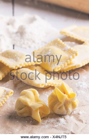 Close up of homemade pasta ravioli and perle on table with flour. - Stock Photo