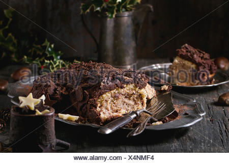 Sliced homemade Christmas chocolate yule log with chestnuts cream on vintage plate with forks,  chocolate stars and holly branch - Stock Photo