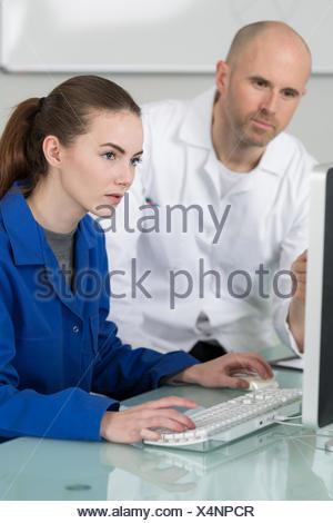 mechanics examining car engine with help of laptop - Stock Photo