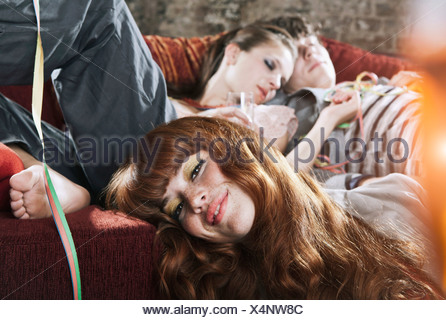 Germany, Berlin, Close up of young man and women relaxing on couch after party - Stock Photo