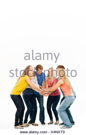 Group of friends about to cheer with their hands stacked smiling as they look at one another - Stock Photo