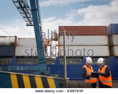 Port Workers In Front Of Loaded Ship - Stock Photo