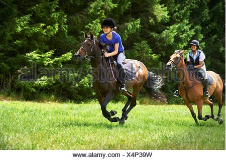 Mature woman and girl galloping on horse - Stock Photo