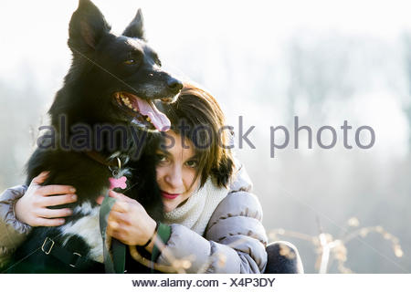 Portrait of mid adult woman hugging her dog - Stock Photo