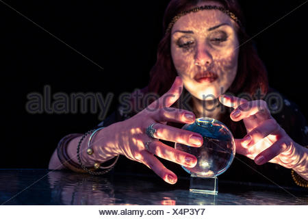 Serious female fortune teller with crystal ball - Stock Photo