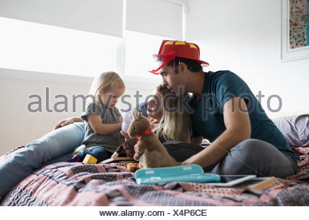 Parents and toddler daughter playing with stuffed animals on bed - Stock Photo