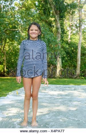 Portrait of young girl standing on slip n slide water mat in garden - Stock Photo