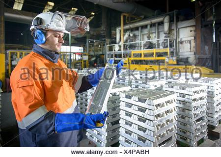 Warehouse worker checking aluminum ingot - Stock Photo