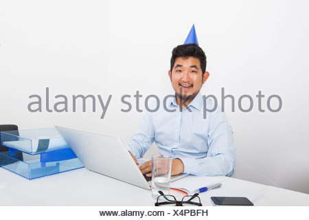Portrait of happy businessman wearing party hat sitting at desk in office - Stock Photo