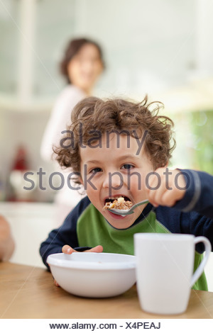 Boy eating breakfast in kitchen - Stock Photo