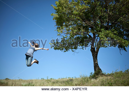Woman jumping by tree - Stock Photo