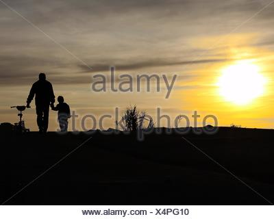 Silhouette Father And Son Walking With Bicycle On Field Against Sunset Sky - Stock Photo