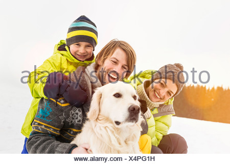 Parents and son with dog in snow - Stock Photo