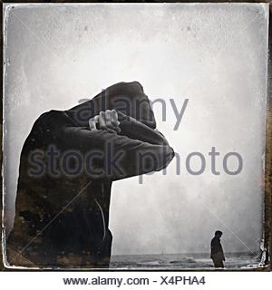 Side View Of Man Hiding Face Against Sea - Stock Photo
