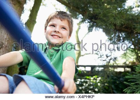 Young Boy sitting on monkey bars, close up - Stock Photo