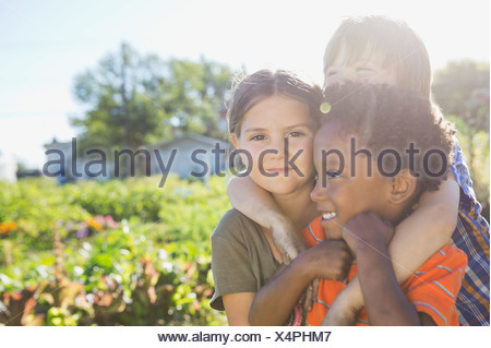 Portrait of cute girl with friends in community garden - Stock Photo