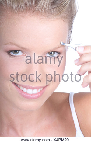 Beauty Care Female long blonde hair worn back off her face, smiling showing teeth, looking at camera, natural make up look, - Stock Photo