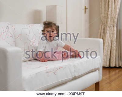 Baby girl using marker on sofa - Stock Photo