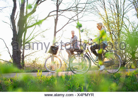 Side view of women cycling on bicycles - Stock Photo