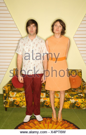Caucasian mid adult couple wearing retro clothes standing stiffly in room decorated with vintage furniture - Stock Photo