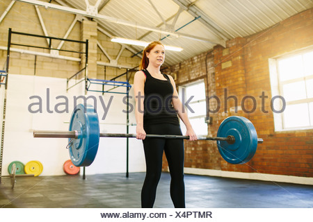 Woman lifting barbell in gym - Stock Photo