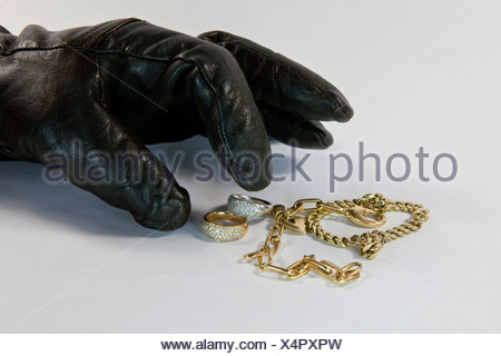 Thief with gloved hand stealing jewelry - Stock Photo