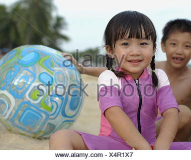 Two young kids outdoors at beach playing with ball - Stock Photo