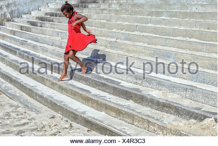 Girl in a red dress running down steps - Stock Photo