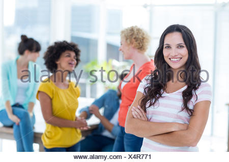 Smiling businesswoman with colleagues in background at office - Stock Photo