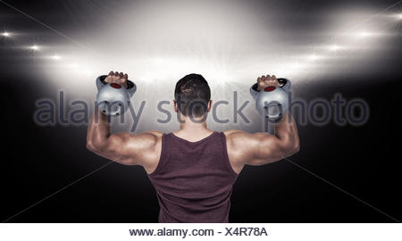 Composite image of rear view of a muscular man lifting kettlebells - Stock Photo