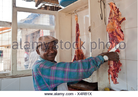 Butcher cutting meat, African man, Tanzania, Africa - Stock Photo