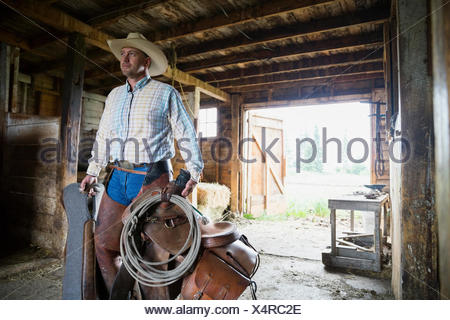 Rancher carrying saddle and tack in barn - Stock Photo
