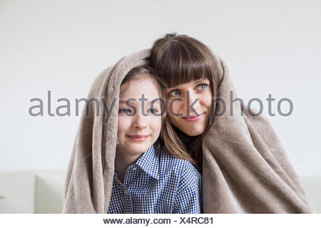 Mother and daughter covered with blanket, smiling - Stock Photo
