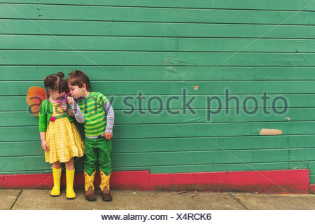 Boy and girl dressed up as a caterpillar and butterfly smelling flowers - Stock Photo