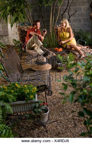 Couple sitting in garden patio drinking wine - Stock Photo
