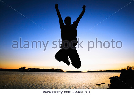 Willmar, Minnesota, United States Of America; Silhouette Of A Person Jumping In The Air By The Water At Sunset - Stock Photo