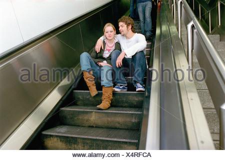 Couple sitting on escalator