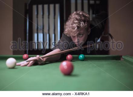 Teenage boy playing snooker - Stock Photo