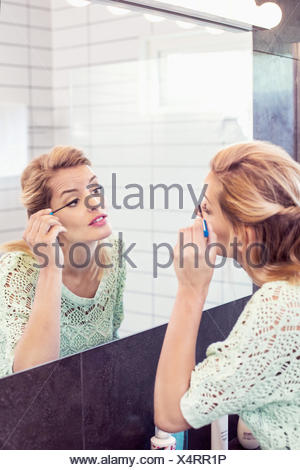 Young woman applying mascara in front of bathroom mirror - Stock Photo