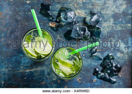 Glass of iced Mojito cocktail with mint on blue background - Stock Photo