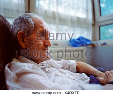 Elderly man in armchair - Stock Photo