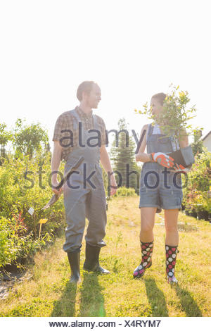 Gardeners conversing at plant nursery - Stock Photo