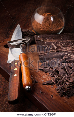 Cut Chocolate bars and cocoa powder on a wooden table - Stock Photo