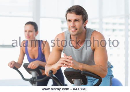Smiling couple working out at spinning class - Stock Photo