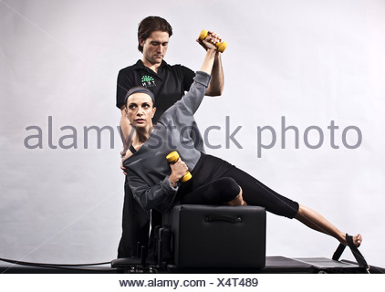Personal trainer and woman on a pilates machine, London, UK - Stock Photo