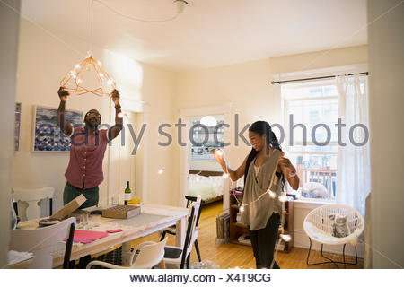 Couple hanging string lights in dining room - Stock Photo