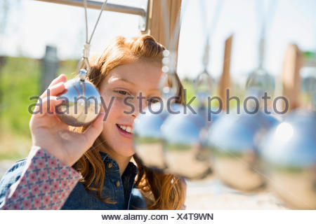 Girl playing with large Newton's Cradle on playground - Stock Photo