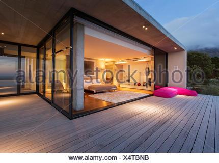 Sliding glass doors onto bedroom of modern house - Stock Photo