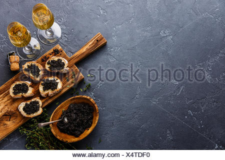 Sturgeon black caviar in wooden bowl, sandwiches and champagne on dark stone background copy space - Stock Photo